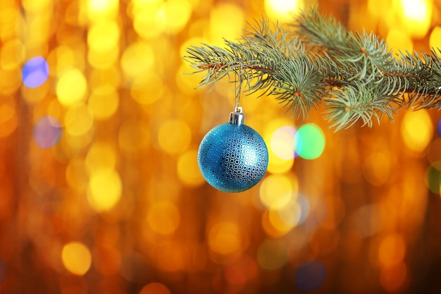 Christmas ball hanging on fir tree branch on blurred golden lights surface