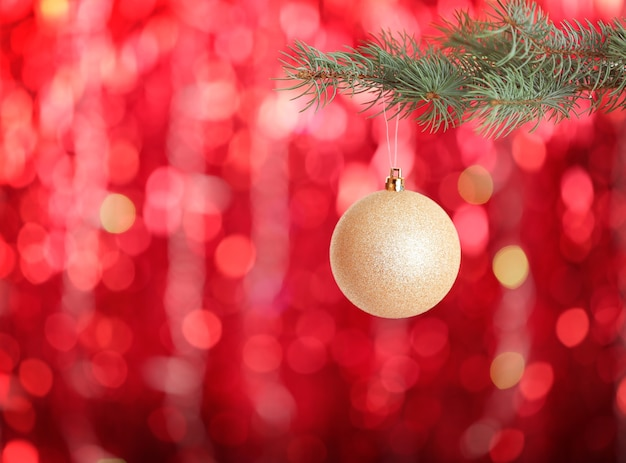 Christmas ball hanging on fir tree branch on blurred red lights background