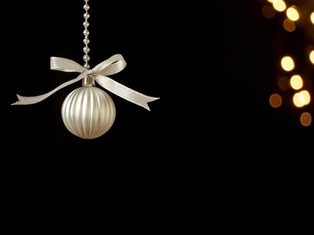 Елочный шар висит на темном фоне против размытых праздничных огней. место для текста