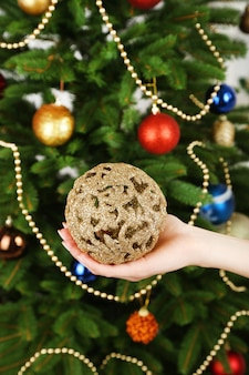 Елочный шар в руке на фоне елки