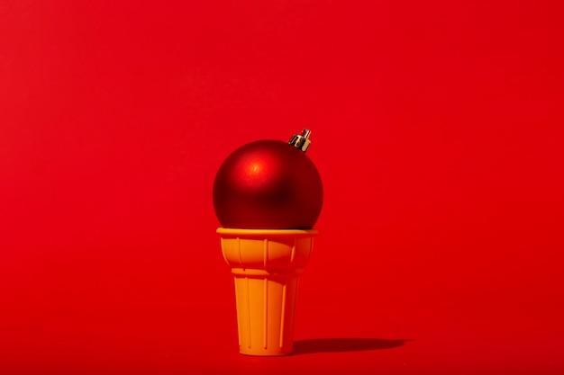 Елочный шар в рожке мороженого на красной стене