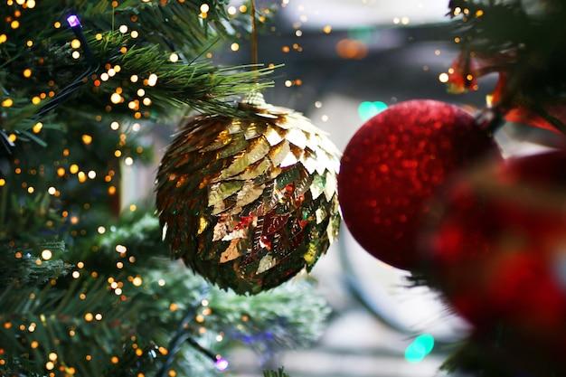 Елочный шар золотого цвета в пайетках, висящий на ветке елки. концепция праздника.