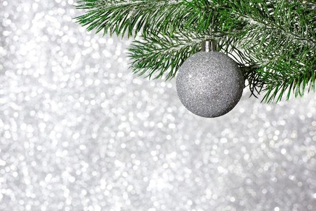 Елочный шар на ветке елки на размытой блестящей поверхности