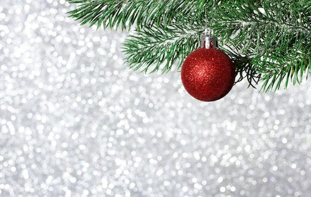 Елочный шар на ветке елки на размытом блестящем фоне