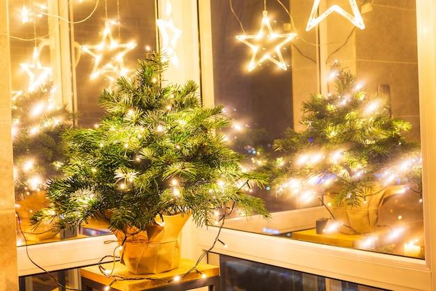 나무 벽 배경에 화환이 있는 크리스마스 트리에 있는 크리스마스 공