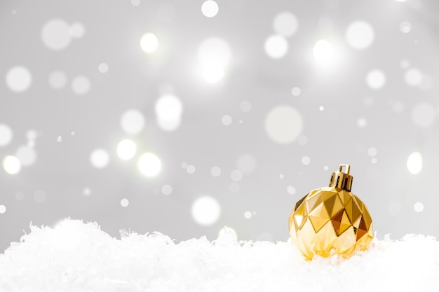 Christmas ball in snow on background of lights. new year concept, place for text.