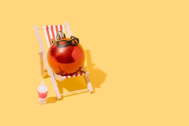 A christmas ball sunbathing on a beach chair summer travel and christmas 3d illustration