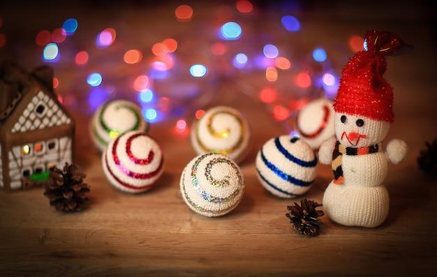 Елочные шары и игрушечный снеговик на рождественском столе