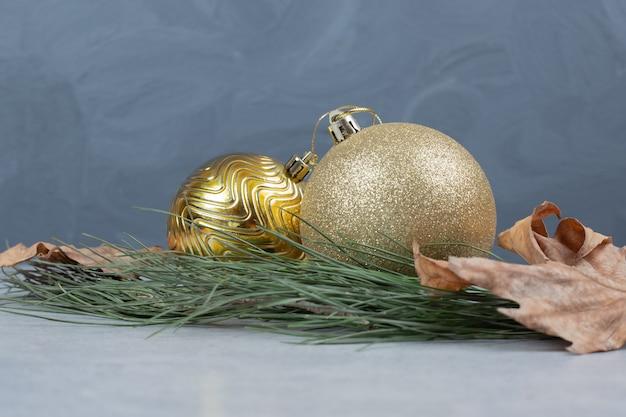 크리스마스 공 및 회색 테이블에 말린 된 잎입니다. 고품질 사진