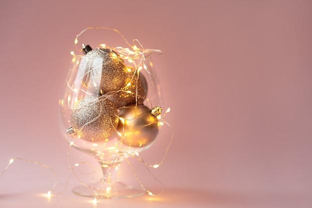 Елочные шары и гирлянды лежат в стеклянной вазе на розовой стене