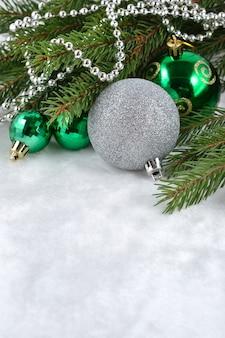 装飾のためのトウヒの枝のクリスマスボールと花輪