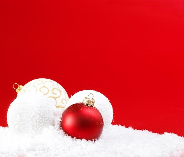 赤い背景の上のクリスマスボールと雪玉