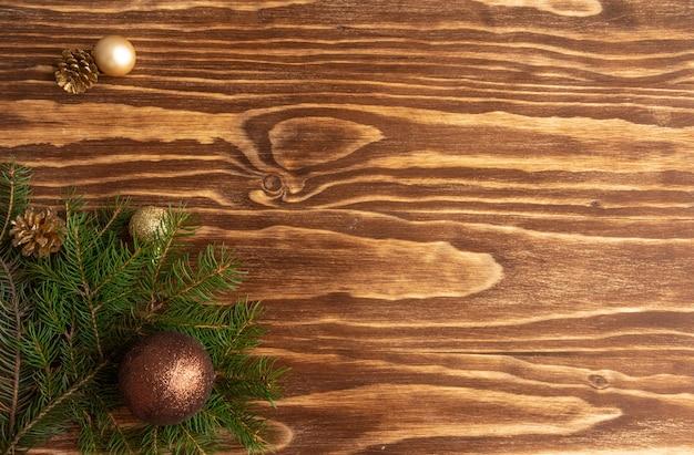 Елочные шары и еловые ветки на деревянном фоне элегантная минималистичная копия пространства