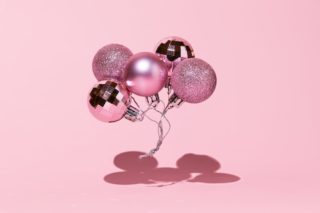 Christmas balls as festive balloons on pink background happy new year 2022 concept still life