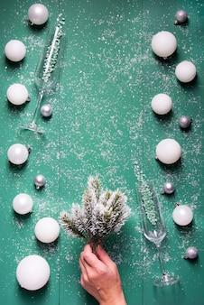 Рождественские шары шампанское бокалы еловые ветки в руке на зеленом деревянном фоне со снегом