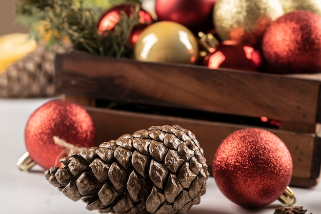 Christmas balls and cones in the wooden box and on the table.