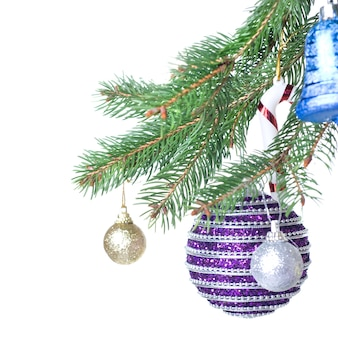 Christmas balls and decoration on fir tree branch isolated on white