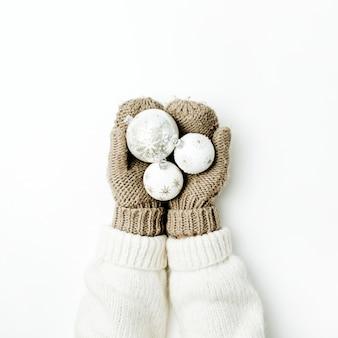 白い表面のニットミトンの女性の手のクリスマスボールの装飾。上面図