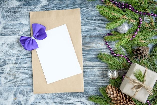 Елочные шары, еловые ветки, шишки, фиолетовый ленточный бант, подарочная коробка и поздравительный конверт на деревянной поверхности .. новогоднее украшение, копия пространства