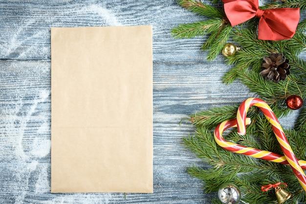 クリスマスボール、モミの枝、コーン、赤いリボンの弓、木の表面にキャンディースティック。クリスマスの装飾、コピースペース