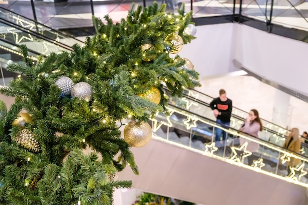 Christmas balls and garland on a decorated fir tree in shopping mall. blurred people on escalator, in festive business center make new year's purchases,.
