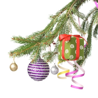 Christmas balls, gift and decoration on fir tree branch isolated on white