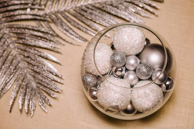 Елочные шары в стекле с серебряной веткой сзади на кремовом фоне