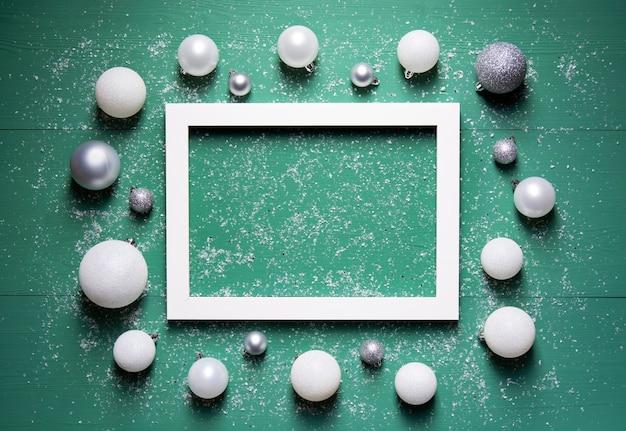 Елочные шары лежат вокруг белой рамки на зеленом деревянном фоне со снегом