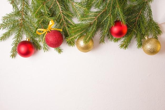 Елочные шары золотого и красного цветов и еловые ветки сверху на белом фоне, вид сверху, копия пространства, рамка из свежих натуральных еловых веток