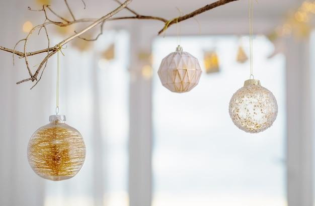 Рождественские шары на золотой ветке на фоне окна