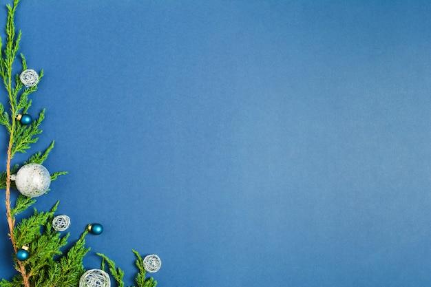 파란색 배경에 전나무 나무의 녹색 지점에 크리스마스 공