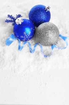 白い背景と雪の上のクリスマスボール
