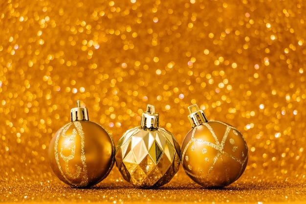 Christmas balls on shiny gold background. new year concept for holiday card. place for text.