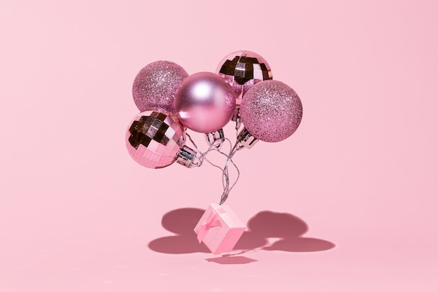 Christmas balls with gift box as a festive balloons on pink background happy new year 2022