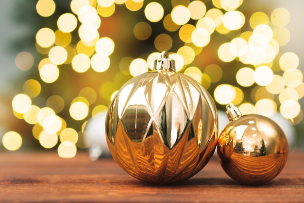 Christmas balls on a wooden table against blurred shiny bokeh background