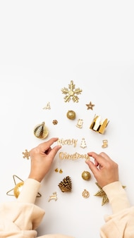 Christmas banner background.woman hand decoration golden color xmas items in christmas tree on table