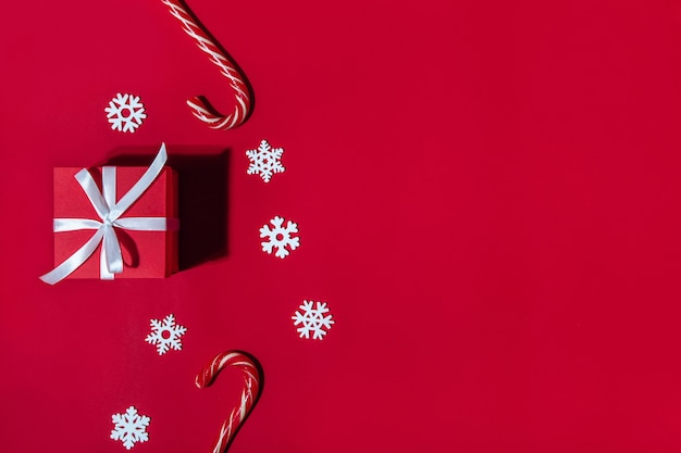 Christmas banner. gift, candy, snowflakes on a red background