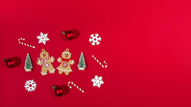 クリスマスバナージンジャーブレッドマンのおもちゃ、キャンディー、ボール、木、赤い背景の雪片