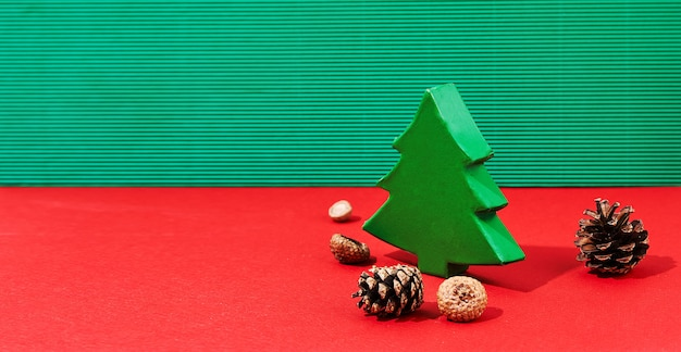 緑のギフトボックスと松ぼっくりのクリスマスバナー。伝統的な色と厳しい影のクリスマスツリー