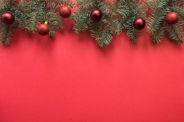Рождественский баннер с еловыми ветками, красные шары на красном пространстве