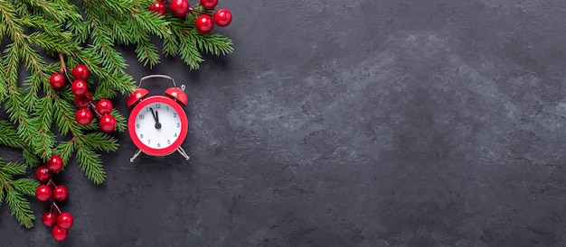 어두운 돌 배경에 전나무, 홀리, 빨간색 알람 시계가 있는 크리스마스 배너. 상위 뷰 복사 공간 - 이미지