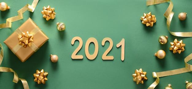 Рождественский баннер с золотым подарком и шарами на зеленом фоне. вид сверху. новогодняя открытка 2021 года.