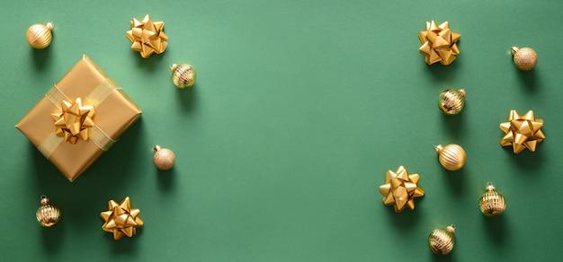 Рождественский баннер с золотым подарком и шарами на зеленом фоне. вид сверху. xmas или новогодняя открытка с копией пространства.