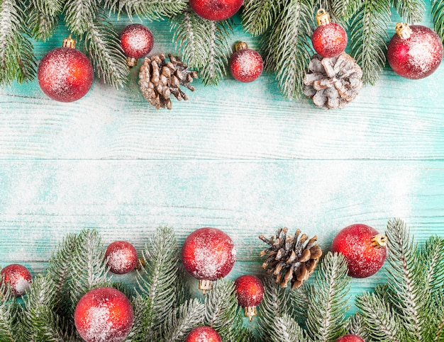 Christmas banner with green tree, ball decorations, cones on wooden textured background under snow