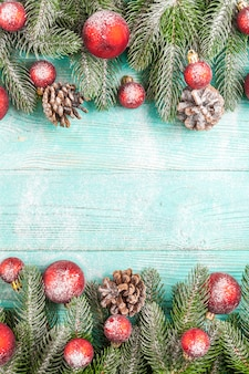 Christmas banner with green tree, ball decorations, cones on wooden textured background