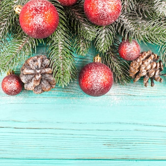 Christmas banner with green tree, red ball decorations, cones on mint wooden background under snow.