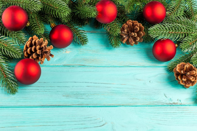 Christmas banner with green tree, red ball decorations, cones on mint wooden background.