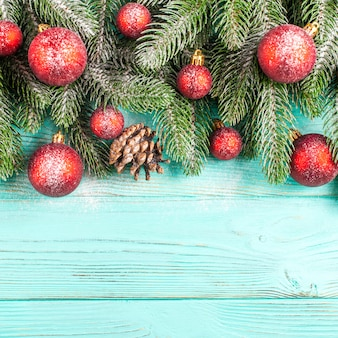 Christmas banner with green tree, red ball decorations, cones on mint wooden background