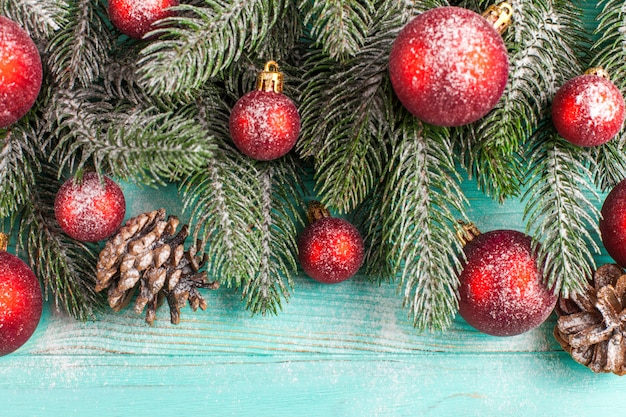 Christmas banner with green tree, red ball decorations, cones on mint wooden textured background