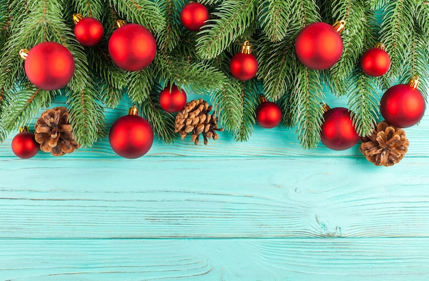 Christmas banner with green tree, red ball decorations, cones on mint wooden textured background.